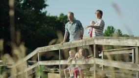 Família feliz com as quatro crianças na ponte no parque HD completo vídeos de arquivo