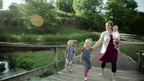 Família feliz com as quatro crianças na ponte no parque HD completo filme