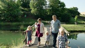 Família feliz com as quatro crianças que andam na ponte no parque HD completo video estoque