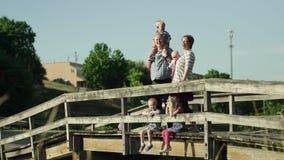Família feliz com as quatro crianças que estão na ponte no parque HD completo video estoque