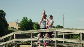 Família feliz com as quatro crianças que estão na ponte no parque HD completo filme