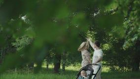 Família feliz com bebê pequeno fora Mãe, pai e bebê tendo o divertimento junto no parque verde do verão vídeos de arquivo
