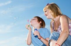 Família feliz com bolhas de sabão de encontro a um céu Fotos de Stock Royalty Free