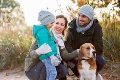 Família feliz com cão do lebreiro fora no outono fotografia de stock