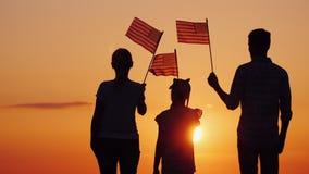 Fam?lia feliz com a crian?a que acena bandeiras dos E.U. no por do sol, vista traseira imagem de stock