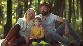 Família feliz com crianças masculinas Pais novos e crianças que têm o piquenique e que relaxam junto em um dia ensolarado dos out video estoque
