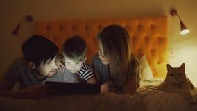 Família feliz com filho pequeno e o gato engraçado que encontram-se na cama em casa e que usam o tablet pc para o filme de observ imagem de stock royalty free