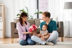 Família feliz com flores e bebê em casa Imagem de Stock