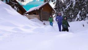Família feliz com jogo do cão do lebreiro em torno da casa de campo de madeira video estoque