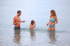 A família feliz com menina espirra as mãos da água Foto de Stock Royalty Free