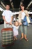 Família feliz com a menina na estação de comboio imagem de stock