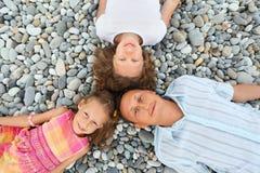 Família feliz com a menina que encontra-se na praia rochoso Imagens de Stock Royalty Free