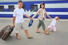 Família feliz com a menina que vai na estação de comboio fotografia de stock