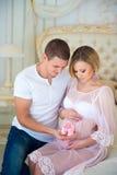 Família feliz com montantes do bebê: marido e esposa grávida que esperam uma criança Foto de Stock
