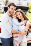 Família feliz com o carro no fundo Fotografia de Stock Royalty Free