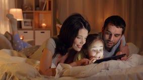 Família feliz com o PC da tabuleta na cama em casa video estoque