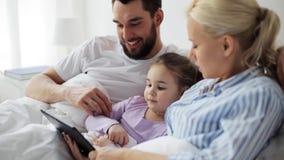 Família feliz com o PC da tabuleta na cama em casa filme