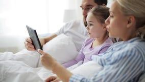 Família feliz com o PC da tabuleta na cama em casa vídeos de arquivo