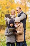 Família feliz com o PC da tabuleta no parque do outono Fotografia de Stock
