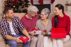 Família feliz com o presente no sofá Foto de Stock Royalty Free
