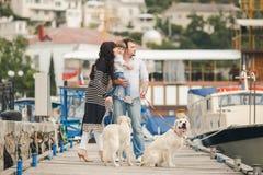 Família feliz com os cães no cais no verão Fotografia de Stock Royalty Free