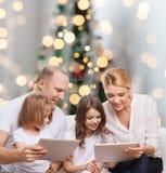 Família feliz com os computadores do PC da tabuleta Fotografia de Stock Royalty Free