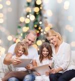 Família feliz com os computadores do PC da tabuleta Foto de Stock