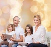 Família feliz com os computadores do PC da tabuleta Imagens de Stock