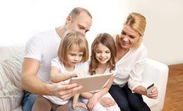 Família feliz com PC da tabuleta e cartão de crédito Fotografia de Stock