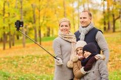 Família feliz com smartphone e monopod no parque Fotografia de Stock