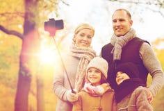 Família feliz com smartphone e monopod no parque Imagens de Stock Royalty Free