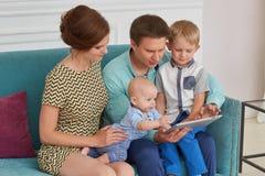 Família feliz com tabuleta do computador Fotografia de Stock Royalty Free