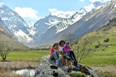 Família feliz com um cão que descansa nas montanhas fotografia de stock royalty free
