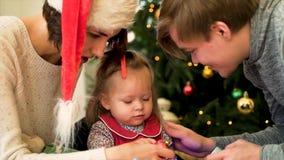 Família feliz com uma criança para gastar junto o Natal Pais e jogo da filha em casa perto da árvore de Natal fotos de stock royalty free