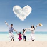 A família feliz corre na praia sob a nuvem do amor Imagem de Stock Royalty Free