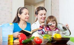 A família feliz cozinha junto com livro de receitas Fotos de Stock