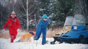 Família feliz da floresta do inverno na roupa colorida que tem o divertimento que joga bolas de neve perto dos carros de neve Mov vídeos de arquivo