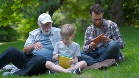 Família feliz da geração três - o pai, o avô e o filho louro sentando-se na grama no parque com livros aprendem ler vídeos de arquivo
