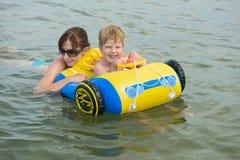Família feliz da mãe com a criança nas ondas no mar Imagem de Stock