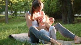 Família feliz da mãe desportiva nova e da filha bonito pequena que têm o divertimento fora video estoque