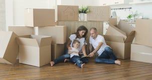 A família feliz das imagens de vídeo move-se em um apartamento novo