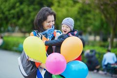 Família feliz de dois com grupo de balões coloridos em Paris imagem de stock