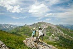 A família feliz de dois meninos e o pai estão estando na rocha nas montanhas imagens de stock