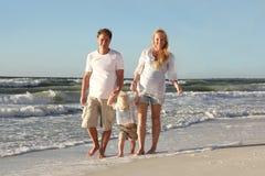 Família feliz de três povos que andam na praia ao longo do oceano Imagens de Stock Royalty Free