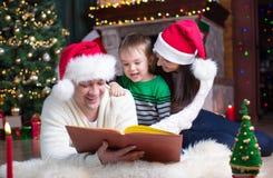 Família feliz do livro de leitura três junto na noite do Natal imagem de stock royalty free