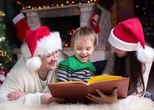 Família feliz do livro de leitura três junto na noite do Natal imagem de stock