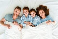 família feliz do ruivo nos pijamas que encontram-se na cama e no sorriso fotografia de stock