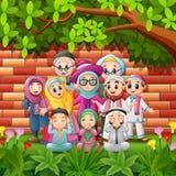 A família feliz dos desenhos animados comemora o eid Mubarak com fundo da parede de tijolo Foto de Stock