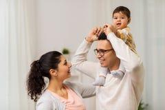 Família feliz e filha do bebê que joga em casa imagem de stock
