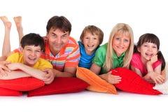 Família feliz em coxins imagem de stock royalty free